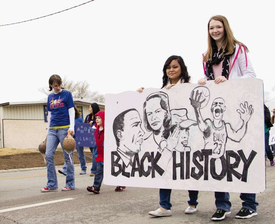 "Two girls hold a sign made by Anderson Elementary minutes before The J-Mac 56th Annual Black History Parade in downtown Conroe Saturday. This is the first year the parade was named after James Garrett, also known as J-Mac who is a radio personality for 97.9 F.M. é'The Boxé"".  Following the parade was an awards ceremony at Booker T. Washington Jr. High School. To view or purchase this photo and others like it, visit HCNpics.com. Photo: Staff Photo By Ana Ramirez, Photographer / The Conroe Courier/ The Woodland"