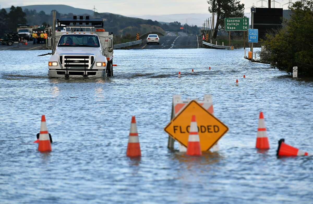 A Caltrans truck drives along a flooded section of Highway 37 in Novato in February 2017. The road was closed for at least 14 days this winter because of flooding and extensive rain.