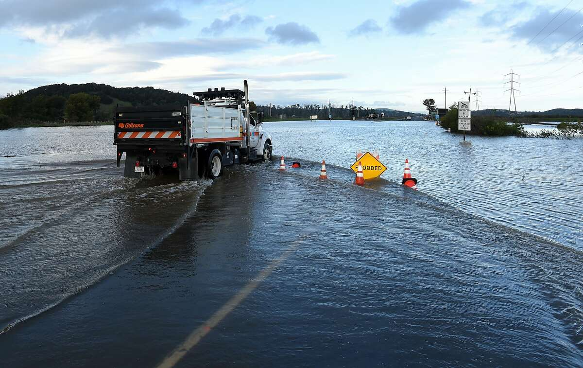 A CalTrans truck drives along a flooded section of Highway 37 in Novato, California on February 10, 2017. The road has been closed at least 14 days this winter due to flooding and extensive rain.