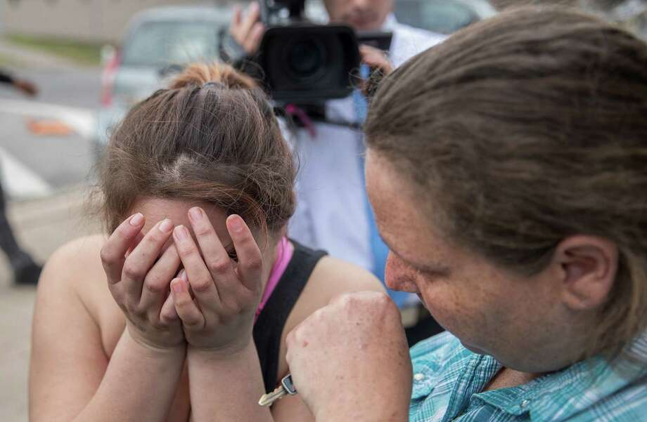 Angle Velazquez is overcome with emotion as she speaks to local media about how the U.S. Immigration and Customs Enforcement arrested her fiance Hugo Baltazar-Ramirez on Friday.  At right, Teresa Velazquez consoles her daughter. Photo: RICARDO B. BRAZZIELL