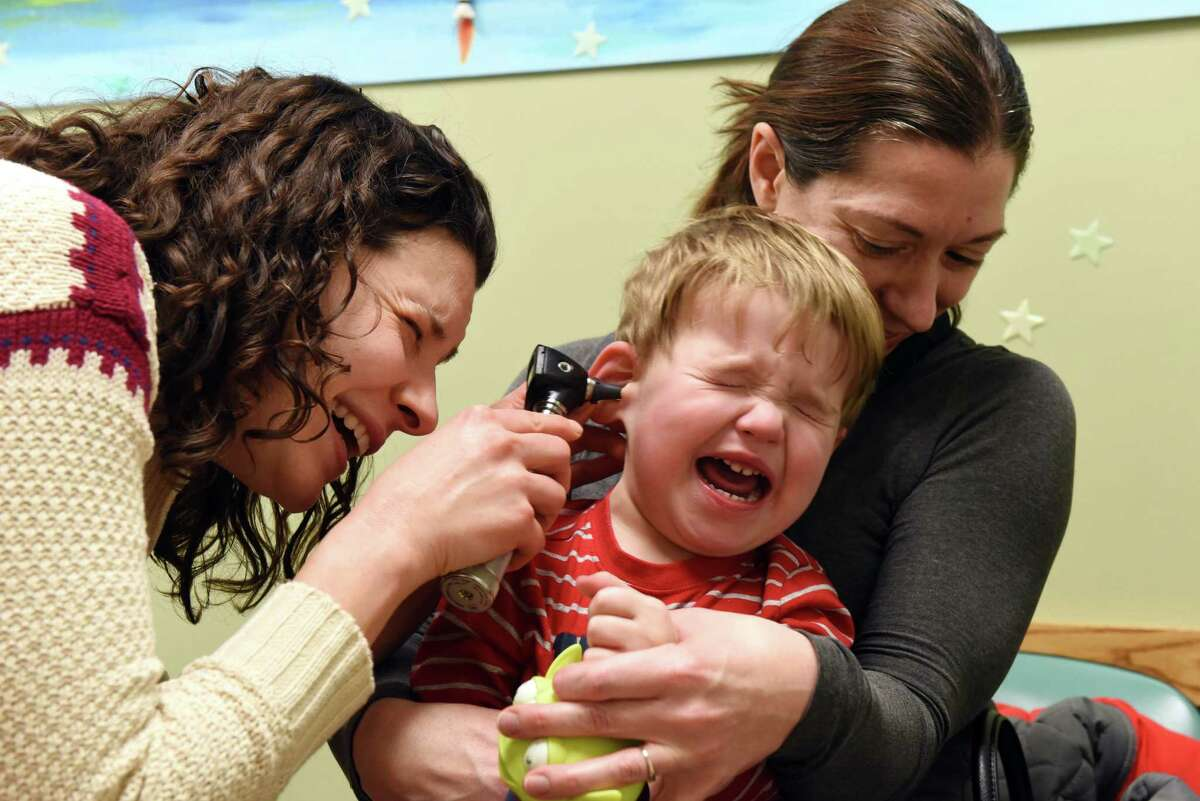 Jacob Andrascik, 2, of Guilderland is held by his mother, Valerie, right, as pediatric nurse practitioner, Brooke Raveendranath, left, takes a look in his ear during a medial exam at CapitalCare Pediatrics on Thursday afternoon, Feb. 9, 2017, in Albany, N.Y.