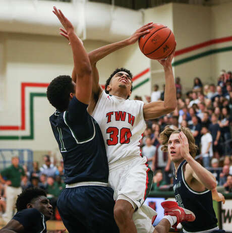 The Woodlands' Sammy Williams, center, puts up a shot despite tight defense by College Park's Jordan Turnquest, left, during Friday night's District 12-6A battle. Photo: Michael Minasi, Staff Photographer / © 2017 Houston Chronicle