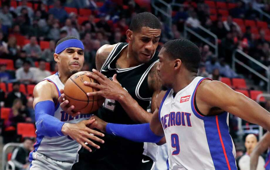 San Antonio Spurs forward LaMarcus Aldridge (12) pulls down a rebound between Detroit Pistons forward Tobias Harris, left, and guard Langston Galloway (9) during the first half of an NBA basketball game, Saturday, Dec. 30, 2017, in Detroit. (AP Photo/Carlos Osorio) Photo: Carlos Osorio, Associated Press / Copyright 2017 The Associated Press. All rights reserved.