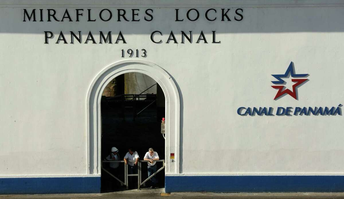 In this Jan. 19, 2017 photo, Panama Canal workers look out from the control tower of the canal's Miraflores locks, in Panama. According to the Panama Canal authority, between June and January there were 15 incidents that resulted in damage to the new expanded locks or ships, or about 2 percent of the 700 total transits. (AP Photo/Arnulfo Franco)