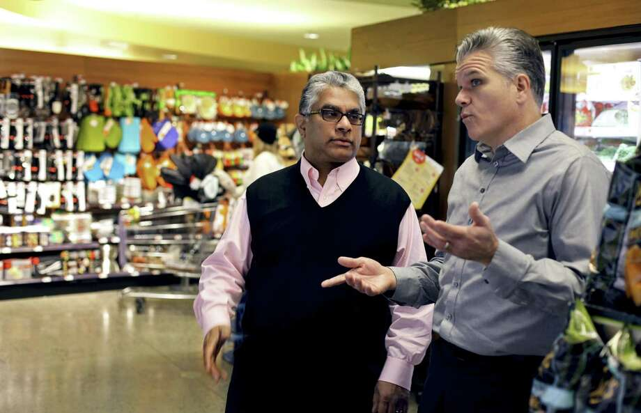 Adnan Durrani, center, chief halal officer with American Halal Co., and Jack Acree, executive vice president, also with American Halal Co., look over their product in a Whole Foods store in Darien in 2010. The company helped Whole Foods develop its first nationally distributed halal (Islamically permitted) food product called Saffron Road entrees. Photo: Craig Ruttle / Associated Press / FR61802 AP