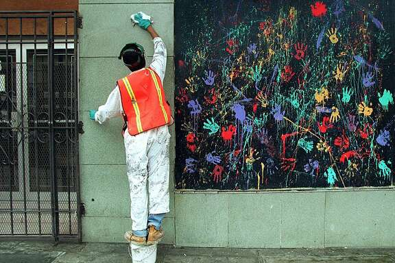 "PAINT PARTY 1/C/19AUG96/CD/CS - SF Department of Public Works employee Lateaf Morton, 24, wipes away graffiti on a wall next to a mural on a building at Golden Gate and Leavenworth in the Tenderloin.  Volunteers were invited to the DPW ""paint party,"" but only DPW workers showed up.  The DPW, SFPD Tenderloin Task Force and the Tenderloin Community on Patrol sponsored the clean-up effort.  SAN FRANCISCO CHRONICLE PHOTO BY CHRIS STEWART"
