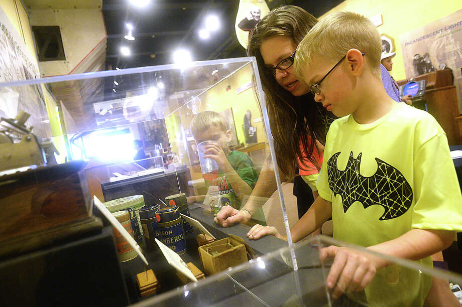 Sarah Screws of Vidor and her children (from right) Ryan and Dylan, take in the exhibits as they tour the Edison Museum during its second annual Edison birthday party event Saturday. A birthday cake and punch and craft activities were included in the celebration of Thomas Edison, whose life-changing scientific achievements included the invention of the light bulb, motion picture camera, telegraphy, and more. Photo taken Saturday, February 11, 2017Kim Brent/The Enterprise Photo: Kim Brent