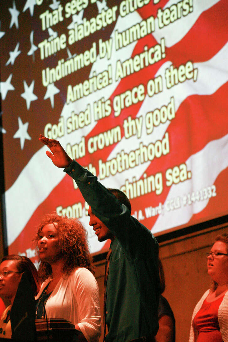 """Jacob Heredia raises his hand as member of the True-Lite Praise Team sing """"America the Beautiful"""" Thursday during the Midland Ministerial Alliance hosted National Day of Prayer at True-Lite Christian Fellowship Church. Cindeka Nealy/Reporter-Telegram"""