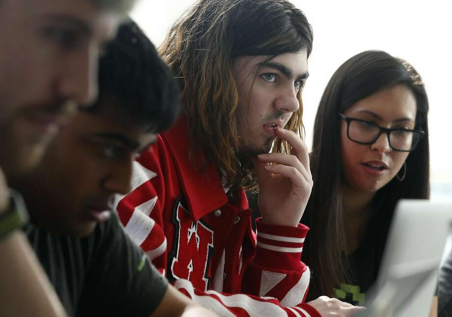Ruby Nealon (center) verifies a possible bug he discovered for Airbnb with Keziah Plattner (right) at the hackathon. Photo: Paul Chinn, The Chronicle