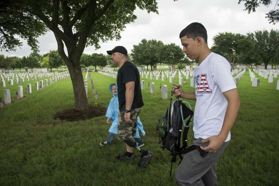 Moses Sonera, a retired Iraq War veteran and amputee, exits Fort Sam Houston National Cemetery with his sons Matthew, 6, left, and Moses Jr., 17, right, after walking from Randolph Air Force Base to the Fort Sam Houston National Cemetery to honor his friends and fellow soldiers who have died, on Memorial Day, Monday, May 25, 2015. Sonera's leg was injured when a mortar exploded from behind him in Iraq in 2004. He says he walked to remind himself of the sacrifice his friends have made. Photo: Matthew Busch, For San Antonio Express-News / For San Antonio Express-News / © Matthew Busch