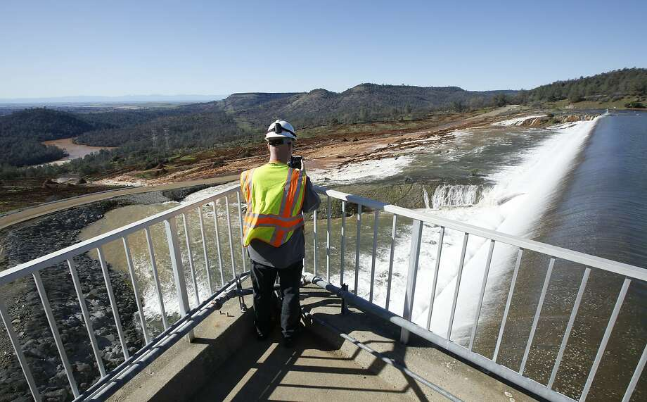 Jason Newton of the Department of Water Resources takes a picture as water pours over the emergency spillway at Oroville Dam for the first time in history. Photo: Rich Pedroncelli, Associated Press