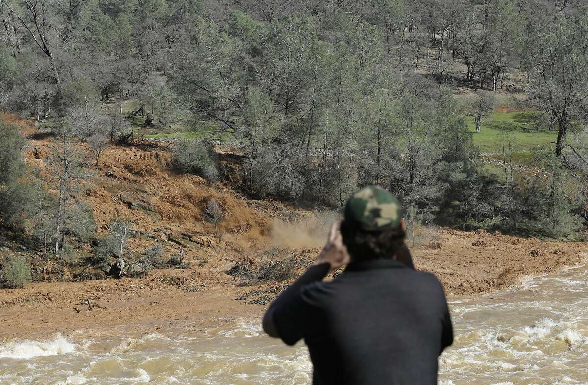 E. Knight uses his smartphone to record muddy water rushing down the emergency spillway at Oroville Dam, Saturday, Feb. 11, 2017, in Oroville, Calif. Water started flowing over the emergency spillway at the nation's tallest dam for the first time Saturday after erosion damaged the Northern California dam's main spillway. (AP Photo/Rich Pedroncelli)
