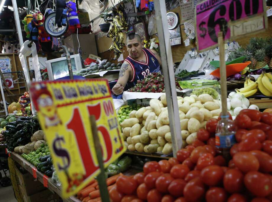 Vendor Luis Alberto Bautista arranges strawberries as he lays out fresh produce at the start of the day, in his vegetable stand in Mercado Medellin, in Mexico City, Thursday, Feb. 2, 2017. Mexico is the worldís leading exporter of refrigerators and flat-screen TVs. Cars and trucks such as the Ram 1500 crew cab, Ford Fiesta and Chevrolet Trax fill U.S. dealer lots. Mexican berries, vegetables and beef born south of the border abound at American supermarkets. (AP Photo/Rebecca Blackwell) Photo: Rebecca Blackwell, STF / Associated Press / Copyright 2017 The Associated Press. All rights reserved.