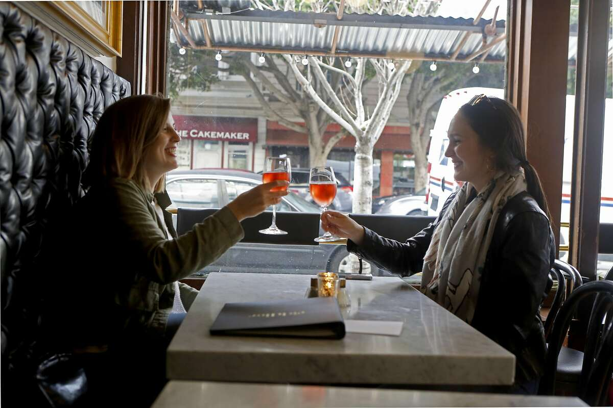 San Francisco residents Katie Hayes, left, and Natalie Williamson, right, cheers their champagne glasses at Riddler, a champagne bar in San Francisco, Calif. on Feb. 10, 2017.
