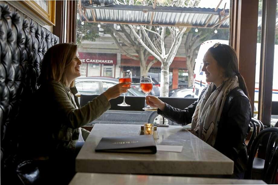 Katie Hayes (left) and Natalie Williamson toast at Riddler. Photo: Natasha Dangond, The Chronicle