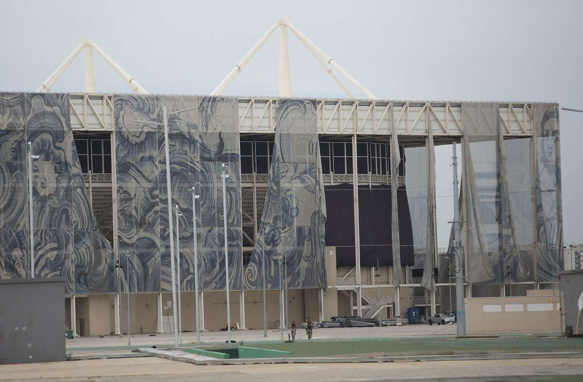 This Feb. 4, 2017 photo shows translucent tapestries created by Brazilian artist Adriana Varejao, falling from the exterior of Olympic Aquatic stadium inside Olympic Park in Rio de Janeiro, Brazil. The Olympic Park is a cutting-edge ghost town; sleek sports arenas without events, deserted before they were even broken in, and well-tended flower gardens, free from pedestrian wear-and-tear.