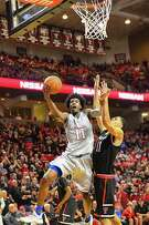 Freshman Josh Jackson, who led Kansas with 31 points and 11 rebounds, charges to the basket against Texas Tech's Zach Smith on Saturday in Lubbock.