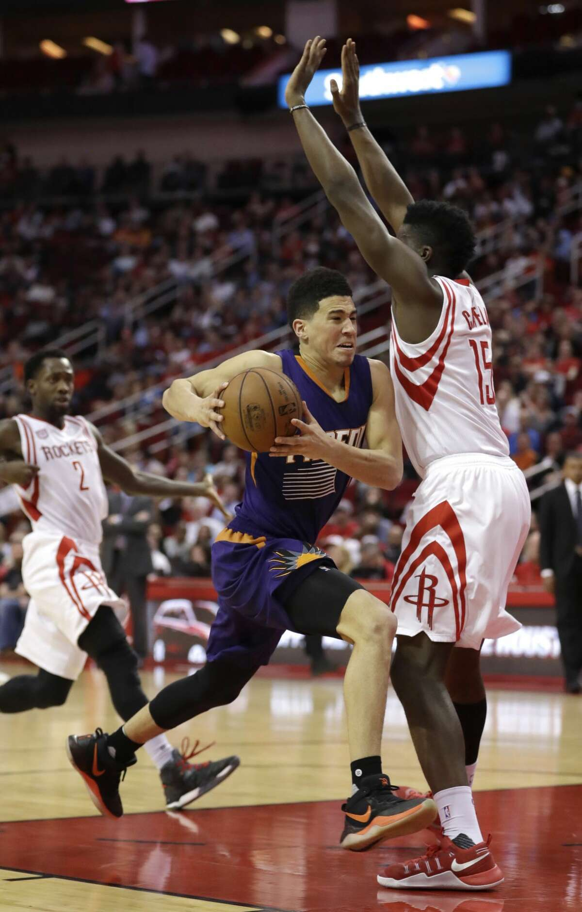 Phoenix Suns' Devin Booker (1) drives toward the basket as Houston Rockets' Clint Capela (15) defends during the second half of an NBA basketball game Saturday, Feb. 11, 2017, in Houston. The Rockets 133-102. (AP Photo/David J. Phillip)
