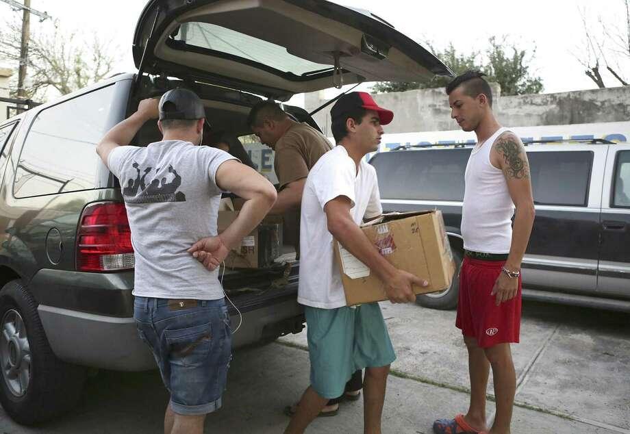 Cubanos ayudan a descargar bolsas de comida y sumistros de un vehículo proveniente de una iglesia bautista de Laredo, TX que serán utilizados en un refugio de Nuevo Laredo, México. Photo: Foto Por Bob Owen|San Antonio Express-News / ©2017 San Antonio Express-News