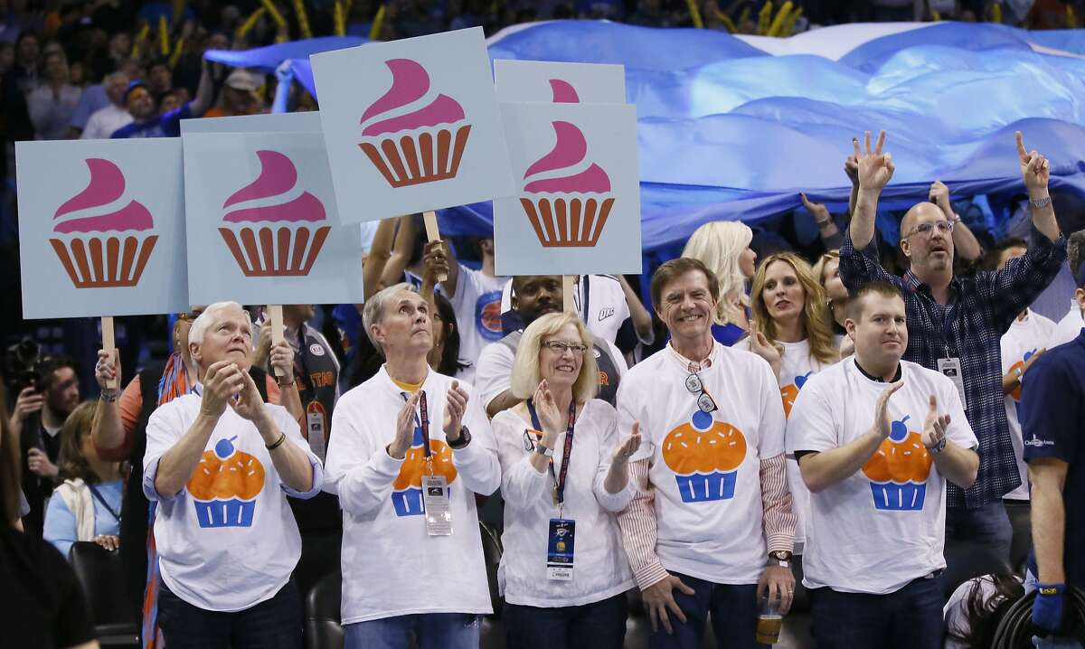 Fans wear cupcake T-shirts and hold cupcake signs in the first quarter of an NBA basketball game between the Golden State Warriors and the Oklahoma City Thunder in Oklahoma City, Saturday, Feb. 11, 2017. (AP Photo/Sue Ogrocki)
