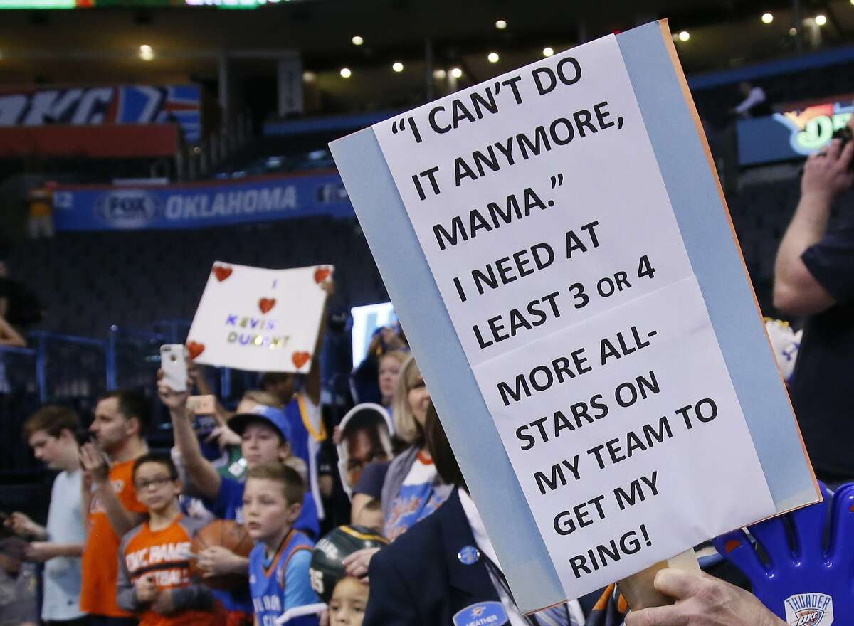 Fans for and against Golden State Warriors forward Kevin Durant react before an NBA basketball game against the Oklahoma City Thunder in Oklahoma City, Saturday, Feb. 11, 2017. (AP Photo/Sue Ogrocki)