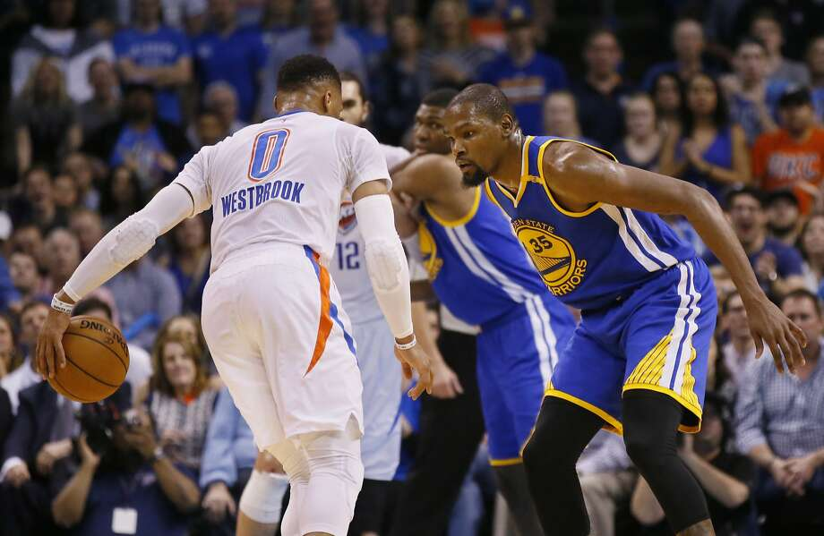 Golden State Warriors forward Kevin Durant (35) defends as Oklahoma City Thunder guard Russell Westbrook (0) dribbles in the first quarter of an NBA basketball game in Oklahoma City, Saturday, Feb. 11, 2017. (AP Photo/Sue Ogrocki) Photo: Sue Ogrocki, Associated Press