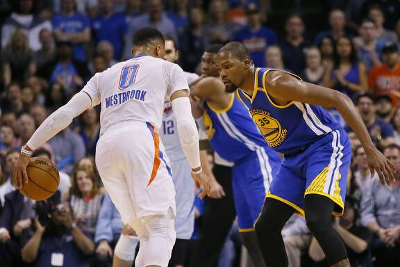 Golden State Warriors forward Kevin Durant (35) defends as Oklahoma City Thunder guard Russell Westbrook (0) dribbles in the first quarter of an NBA basketball game in Oklahoma City, Saturday, Feb. 11, 2017. (AP Photo/Sue Ogrocki)