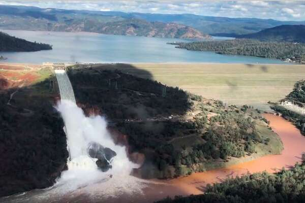 A Friday, Feb. 10, 2017, image from video provided by the office of Assemblyman Brian Dahle shows water flowing over the primary spillway of the Oroville Dam before the emergency spillway was activated on Saturday.