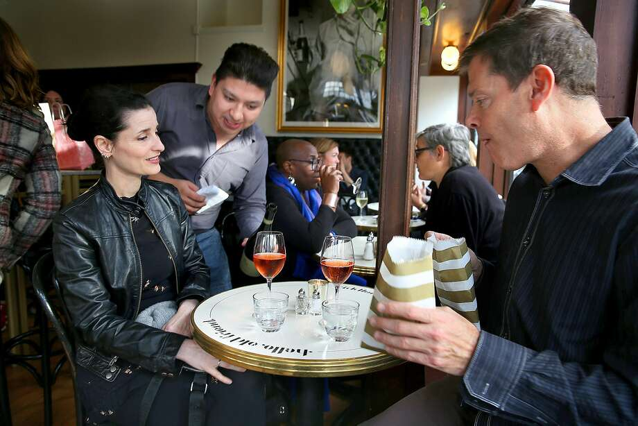 Assistant sommelier Akoni Lagua (middle) pours Champagne for Jane Reingold as her friend holds popcorn at the Riddler in S.F. Photo: Liz Hafalia, The Chronicle