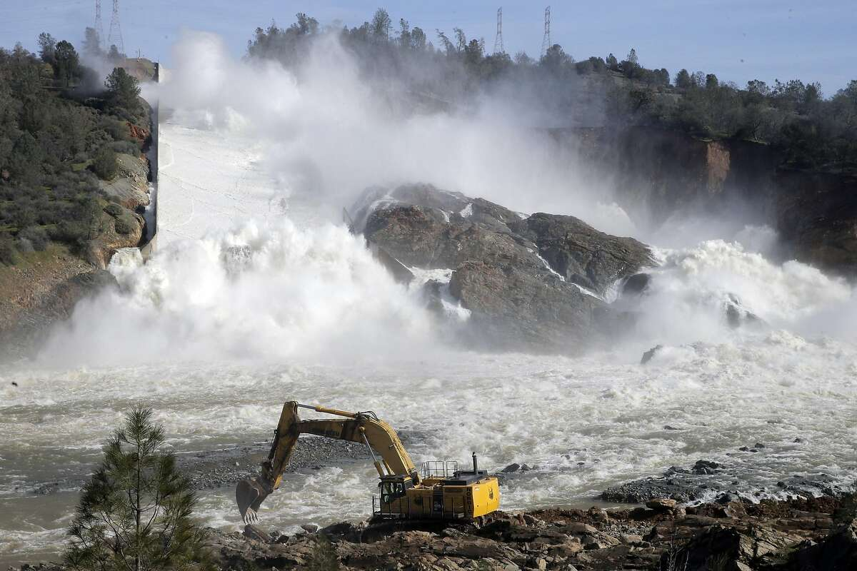 An excavator moves dirt and rocks to level off an area along the banks of the Feather River to creat a road for other heave equipment that will be used to clear debris from the river as thousands of gallons of water rush over the auxiliary spillway at Oroville Dam in Oroville, Calif., on Sunday, February 12, 2017. The California Department of Water Resources is now working to remove debris from the river so water flow down the Feather River doesn't impede the hydroelectric generation at the dam.