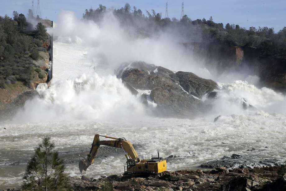 An excavator moves dirt and rocks to level off an area along the banks of the Feather River to creat a road for other heave equipment that will be used to clear debris from the river as thousands of gallons of water rush over the auxiliary spillway at Oroville Dam in Oroville, Calif., on Sunday, February 12, 2017. The California Department of Water Resources is now working to remove debris from the river so water flow down the Feather River doesn't impede the hydroelectric generation at the dam. Photo: Carlos Avila Gonzalez, The Chronicle