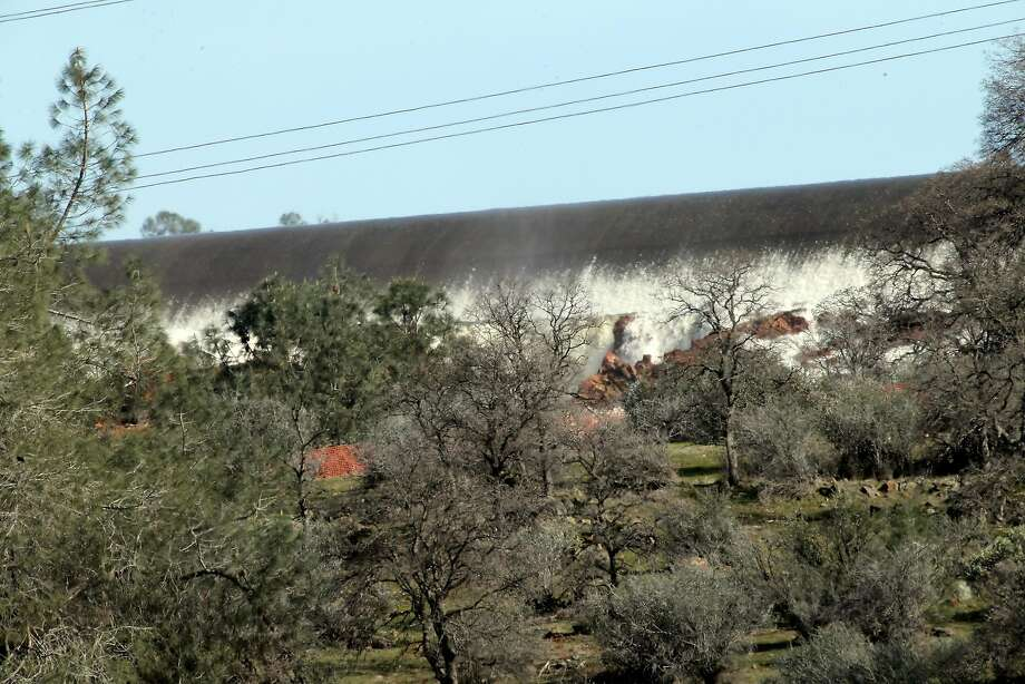 Water rushed over the side of the auxiliary spillway at Oroville Dam in Oroville, Calif., on Sunday, February 12, 2017. The California Department of Water Resources is now working to remove debris from the river so water flow down the Feather River doesn't impede the hydroelectric generation at the dam. Photo: Carlos Avila Gonzalez, The Chronicle