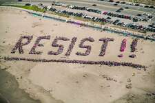 "Protesters gather to spell out ""Resist!!"" on Ocean Beach in San Francisco on Jan. 11, 2017."