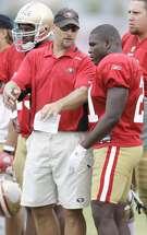 San Francisco 49ers running backs coach Tom Rathman, left, talks to running back Frank Gore during NFL football training camp in Santa Clara, Calif., Monday, Aug. 3, 2009. (AP Photo/Jeff Chiu)