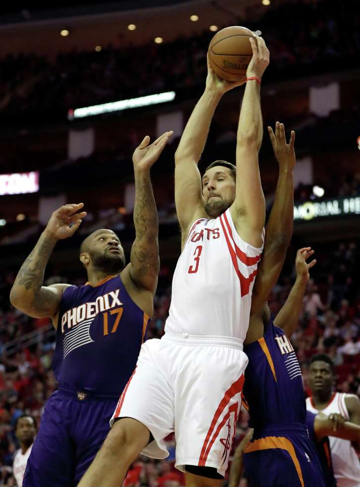 The Rockets' Ryan Anderson comes up big in a battle with P.J. Tucker (17) for a rebound Saturday night.