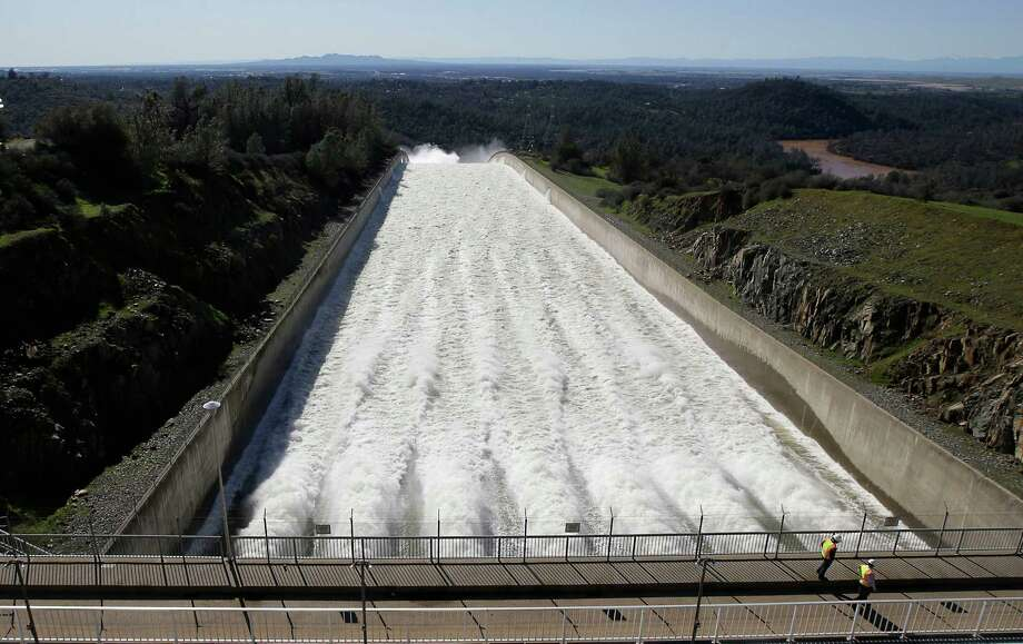 In this Saturday, Feb. 11, 2017, photo, water flows down Oroville Dam's main spillway, in Oroville, Calif. Water began flowing over the emergency spillway on Saturday for the first time in its nearly 50-year history after heavy rainfall. In addition to the emergency spillway, water also flowed through the main spillway that was significantly damaged from erosion. Officials said they'll assess the damage starting Monday. (AP Photo/Rich Pedroncelli) Photo: Rich Pedroncelli, STF / Copyright 2017 The Associated Press. All rights reserved.
