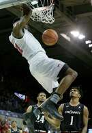 SMU's Ben Emelogu dunks over a pair of Cincinnati defenders for two of his 11 points in Sunday's win at Dallas.