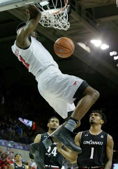 SMU's Ben Emelogu dunks over a pair of Cincinnati defenders for two of his 11 points in Sunday's win at Dallas. Photo: LM Otero, STF / Copyright 2017 The Associated Press. All rights reserved.