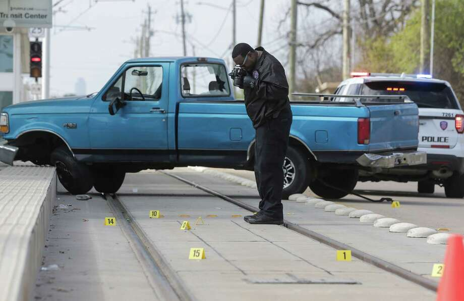 A Houston Police Dept. officer photographs a shooting scene where a truck ran into the Metro Line on  Griggs Road on Sunday. According to police two groups of men in vehicles exchanged gunfire. Photo: Elizabeth Conley, Staff / © 2017 Houston Chronicle