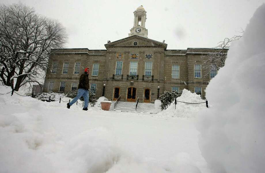 A passer-by walks on a snow-covered sidewalk in front of Waltham City Hall, Sunday, Feb. 12, 2017, in Waltham, Mass. (AP Photo/Steven Senne) Photo: Steven Senne, STF / AP