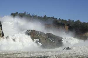 """In this Saturday, Feb. 11, 2017, water flows down Oroville Dam's main spillway, near Oroville, Calif. Officials have ordered residents near the Oroville Dam in Northern California to evacuate the area Sunday, Feb. 12, saying a """"hazardous situation is developing"""" after an emergency spillway severely eroded. (AP Photo/Rich Pedroncelli)"""