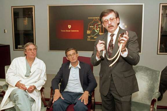 Heart surgeon Dr. Bud Frazier and patient Mike Templeton watch as Victor Poirier, developer of the HeartMate, explains the portable, battery-powered ventricular assist device to the media on Oct. 1, 1991, at the Texas Heart Institute.