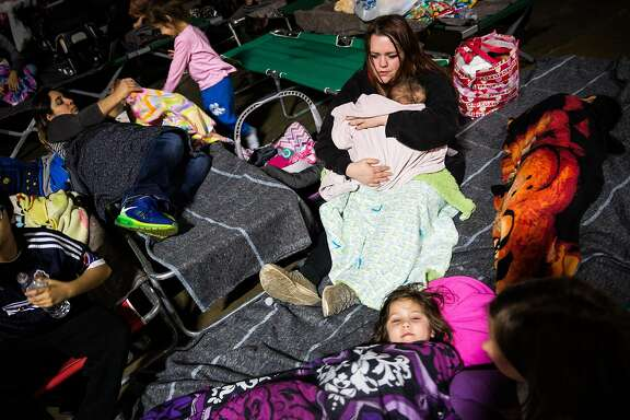 Gridley resident Shari Mota, right, tries to get her children to go to sleep in the evacuation center at the Butte County Fairgrounds in Chico, California on February 12, 2017.