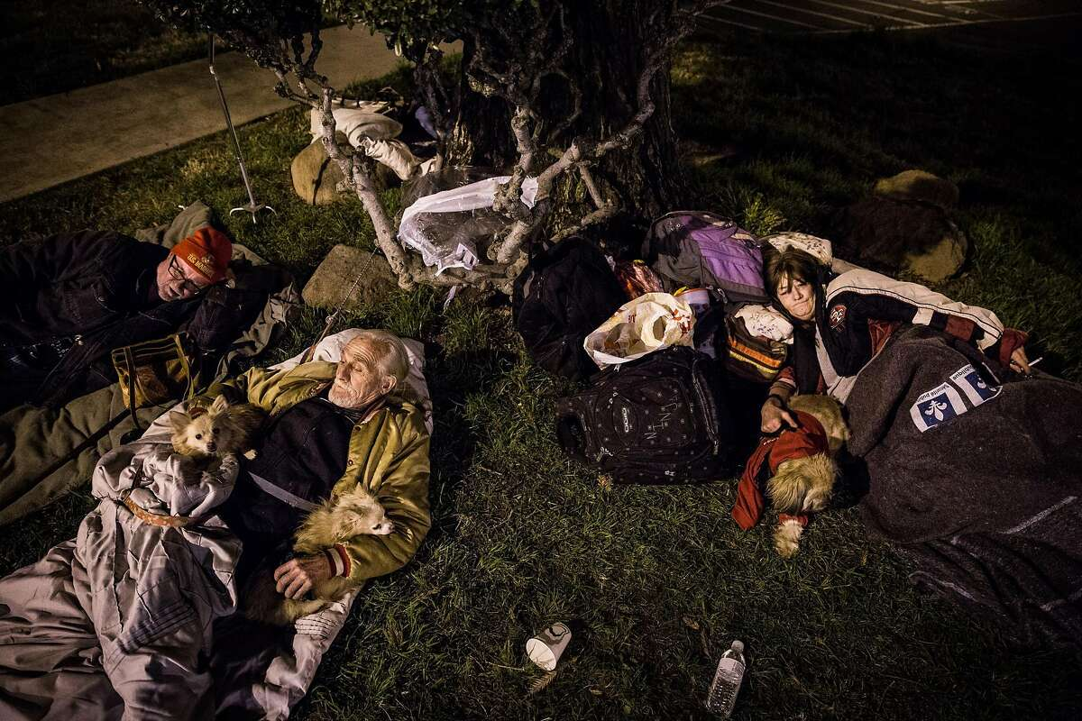 From left, Oroville residents Georgia Robert King, Jerry Lee Huggins and Anna Gibson sleep outside the evacuation center at the Butte County Fairgrounds in Chico, California on February 12, 2017. Pets aren't allowed in the evacuation center, so many pet owners stayed in their cars in the parking lot.