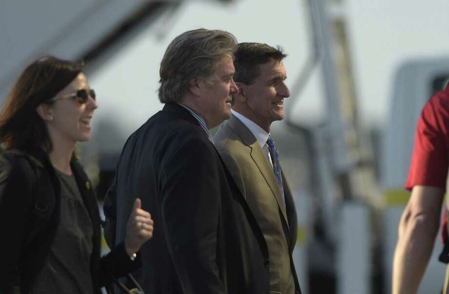 White House strategist Stephen Bannon, second from left, and National Security Adviser Michael Flynn, right, prepare to board Air Force One at Palm Beach International Airport in West Palm Beach, Fla., Sunday, Feb. 12, 2017. Trump spent the weekend at his Mar-a-Lago estate hosting Japanese Prime Minister Shinzo Abe and playing golf. (AP Photo/Susan Walsh) Photo: Susan Walsh, STF / Associated Press / Copyright 2017 The Associated Press. All rights reserved.