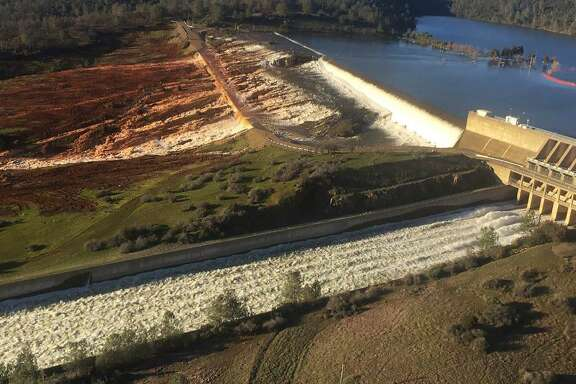 This Feb. 11, 2017, photo released by the California Department of Water Resources shows the main spillway, bottom, and an auxiliary spillway, upper, of the Oroville Dam at Lake Oroville in Oroville, Calif.
