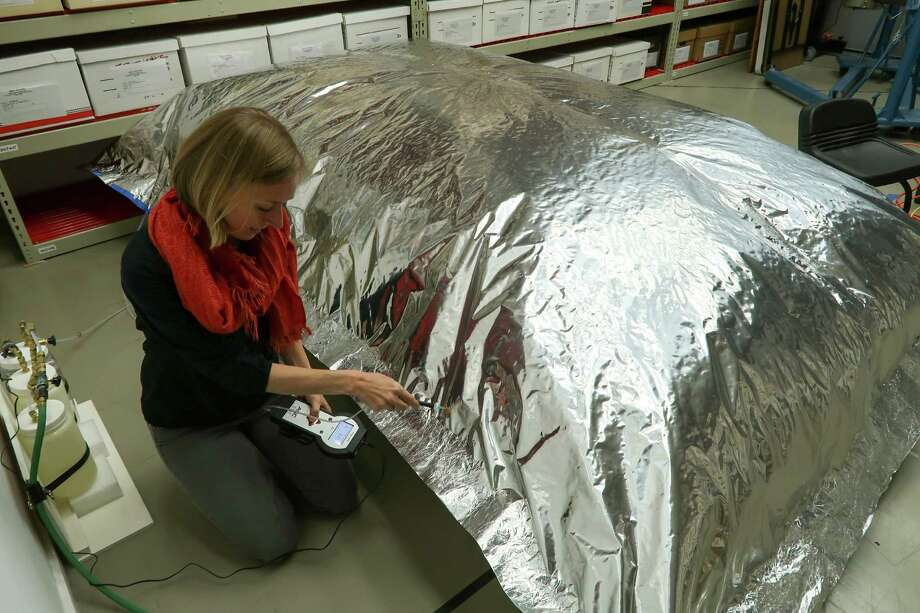 """Objects conservator Kari Dodson checks the readings on an """"anoxia capsule"""" with zero-oxygen conditions that was created to sterilize and de-bug wooden sculptures from Africa for 7-8 weeks before they could go on display at the Menil Collection. Photo: Menil Collection"""