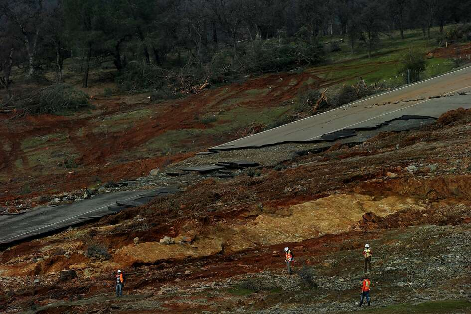 Officials investigate the emergency spillway of the Oroville Dam for damage on Monday, Feb. 13, 2017 in Oroville, Calif. Nearly 200,000 people downriver from Lake Oroville were ordered to evacuate Sunday night, after an emergency spillway next to the reservoir�s dam appeared in danger of collapse.
