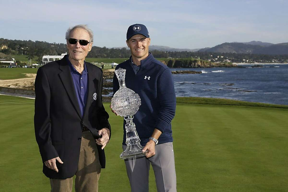 Jordan Spieth, right, poses with Clint Eastwood, left, on the 18th green of the Pebble Beach Golf Links after winning the AT&T Pebble Beach National Pro-Am golf tournament Sunday, Feb. 12, 2017, in Pebble Beach, Calif. Spieth won the tournament by four strokes and finished at total 19-under-par. (AP Photo/Eric Risberg)