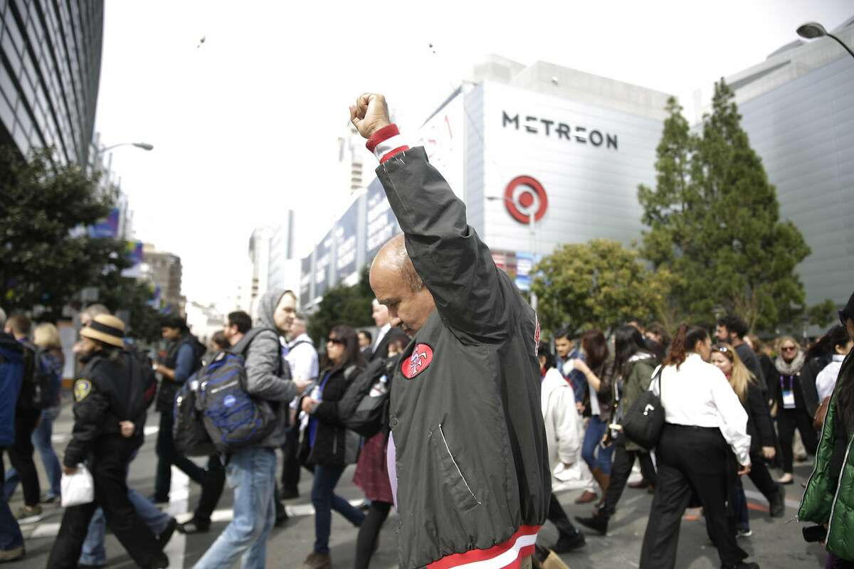 Jorge Castillo, security guard Valley Transportation Authority, holds his fist in the air as he crosses Fourth Street after attending a rally to call on the tech industry to support all tech workers and to celebrate the 9th Circuit Court's decision to refuse to reinstate Trump's travel ban on Monday, February 13, 2017 in San Francisco, Calif.